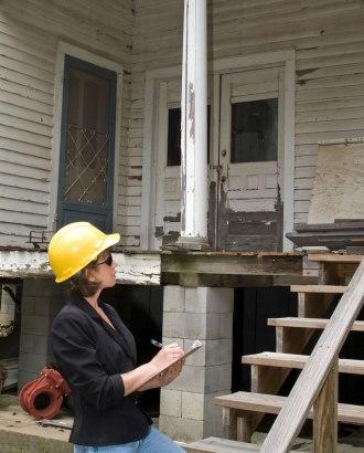 Adjuster evaluates a damaged house