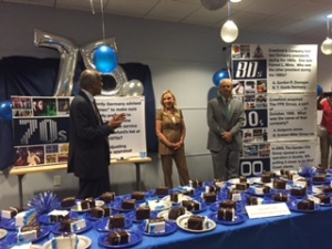 Harsha V. Agadi (left), Crawford & Company interim president and CEO, speaks to Atlanta Support Center employees Tuesday during a celebration of cake and camaraderie to commemorate the Company's 75-year anniversary. Also pictured are Jesse C. Crawford, Sr. and his wife, Sherry. Jesse, son of Crawford Founder Jim Crawford, is chairman of the Crawford Board of Directors Executive Committee and president and CEO of Crawford Media Services, Inc.