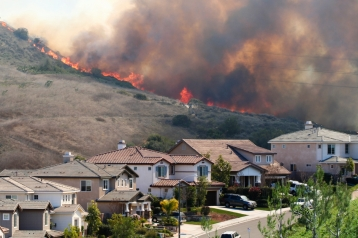 A California brush fire burns close to homes.