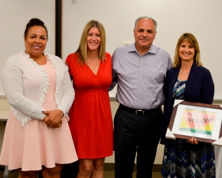 Broadspire's Erica Fichter, SVP, Medical Management, far right holding a picture next to Neil Lentine, COO of Claims & Client Services, Broadspire.  The other two women pictured are from SOS.